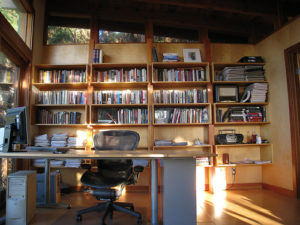 picture of desk and chair in front of a book case
