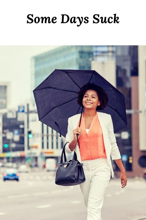 """African American woman with umbrella and the word """"Some Days Suck"""""""